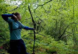 woman shooting a bow in a forest